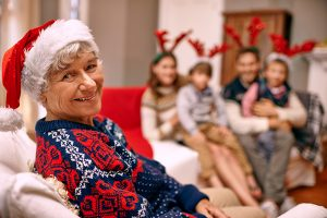 Grandma wearing Santa hat with family in background