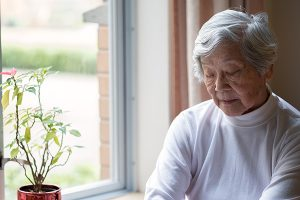 Lonely, Senior Woman Sitting by Window with Eyes Closed