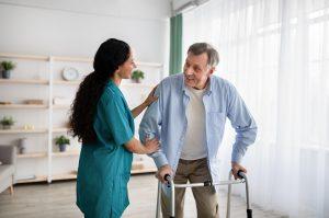 Young Nurse Helping Older Man