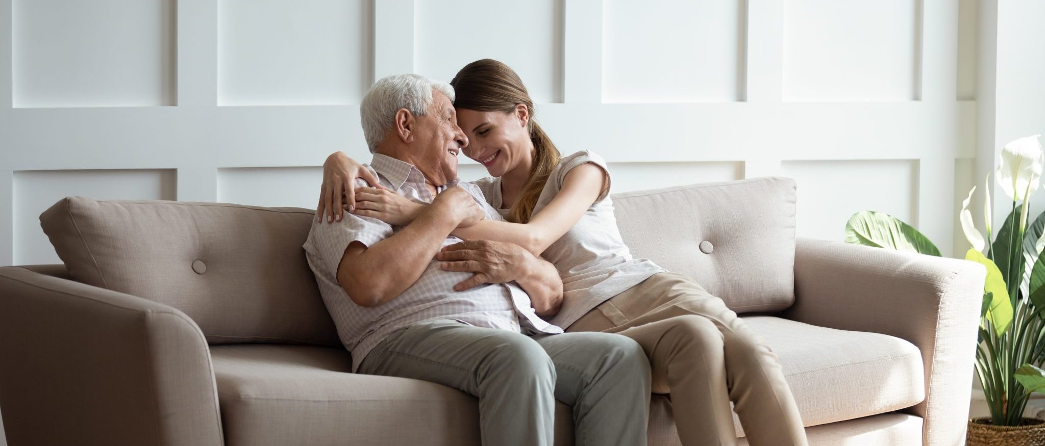 a daughter and her father embracing happily on a couch