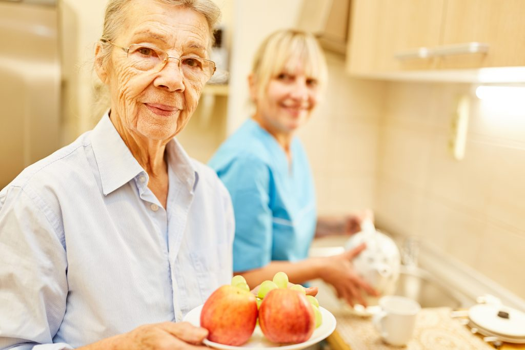 senior woman gets assistance with meal preparation from in-home caregiver
