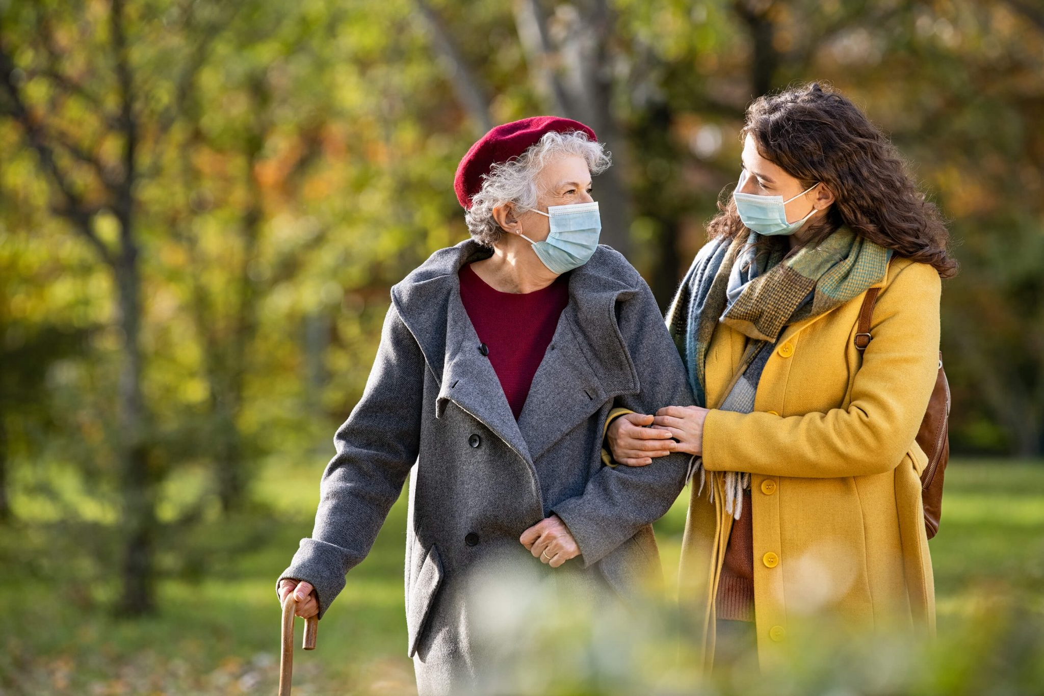 an older loved one and caregiver take a walk