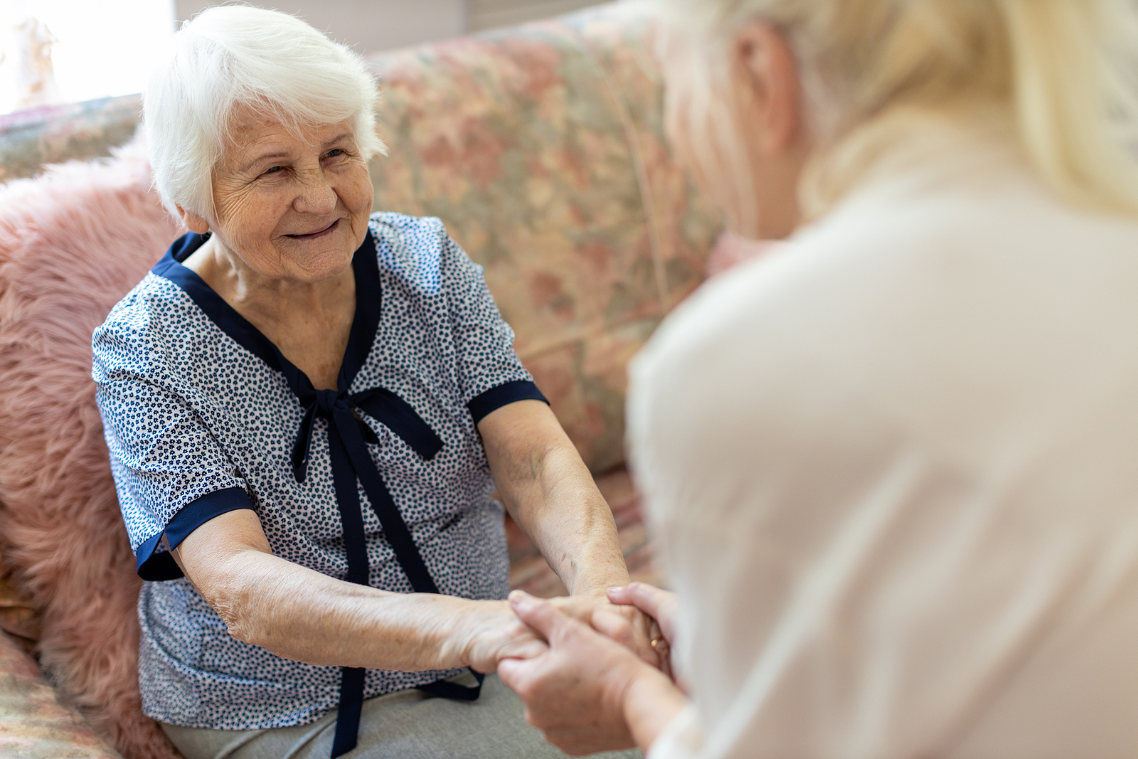 an in-home caregiver helps a senior woman stand up.