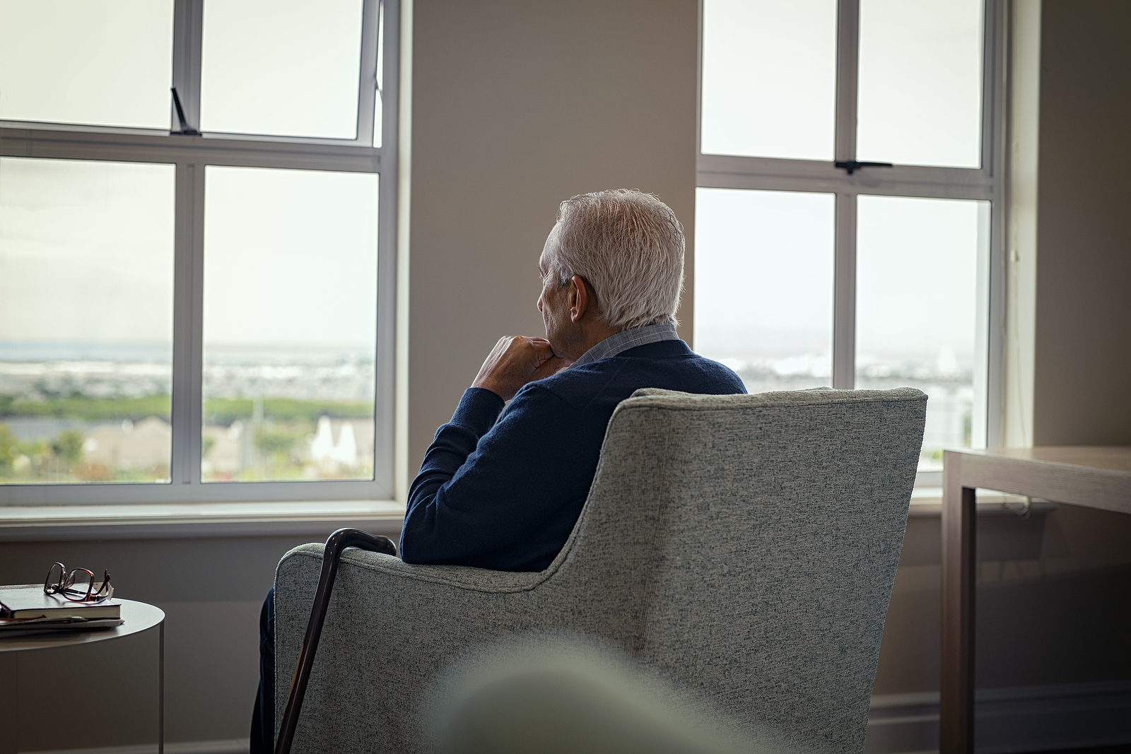 rear view of an elderly man sitting alone in an armchair looking out the window