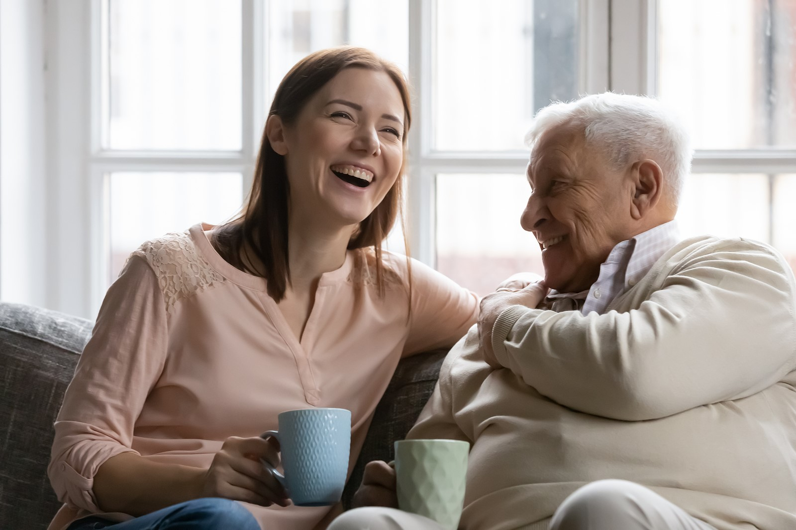 a young woman sitting with her elderly father smiling and laughing while enjoying a cup of coffee